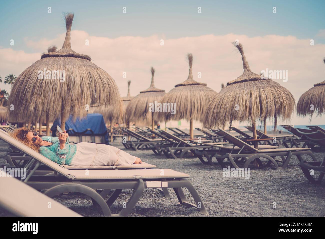 Schönen kaukasischen Frauen mittleren Alters auf die Sitze legen am Strand mit tropischen Sonnenschirme. Reisen und Ferien rest Konzept. Bleiben Sie verbunden wit Stockbild