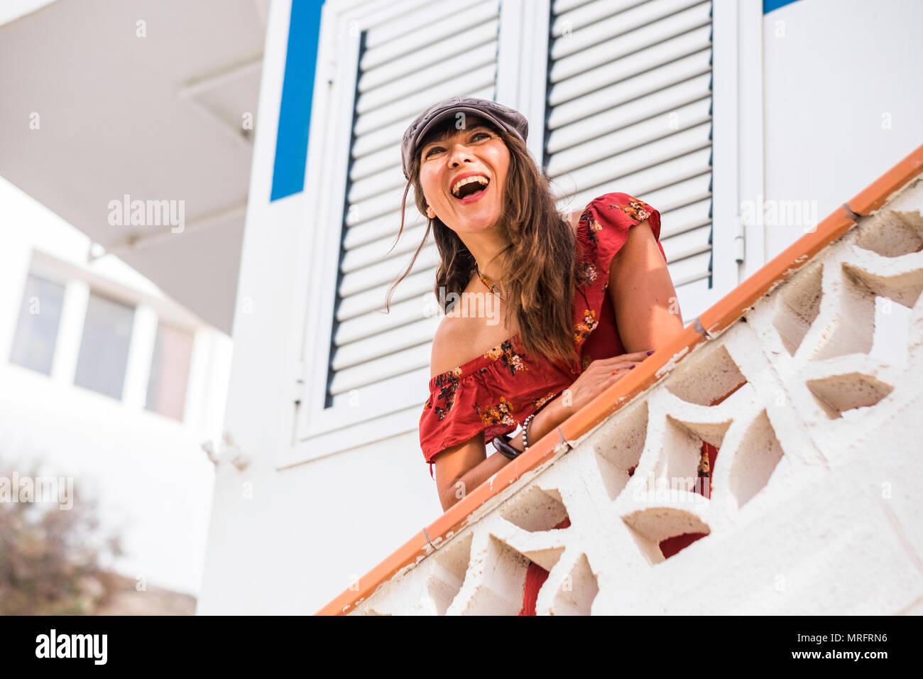 Lächeln und Lachen für Glück und genießen Konzept mit einem schönen 40 Jahre alt, Kaukasier, mit weißen Häusern im Hintergrund. Freizeit n Stockbild