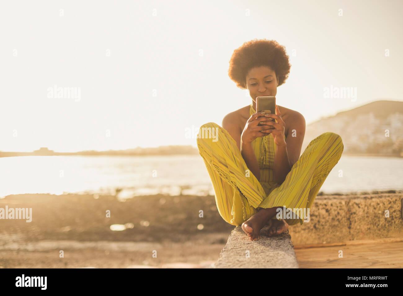 Schönen schwarzen Rasse afrikanische Modell mit schönem Haar mit dem Smartphone sitzen in der Nähe von das Meer und den Strand in Freiheit Freizeit Urlaub Aktivität. conta Stockbild