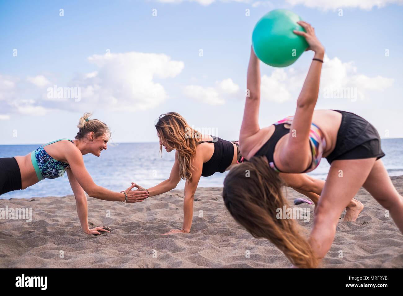 Gruppe von Frauen Menschen kaukasischen drei schöne Frauen Yoga und Fitness auf dem Sand am Strand in der Nähe des Meeres. Freiheit Konzept für Freizeitaktivitäten ac Stockbild