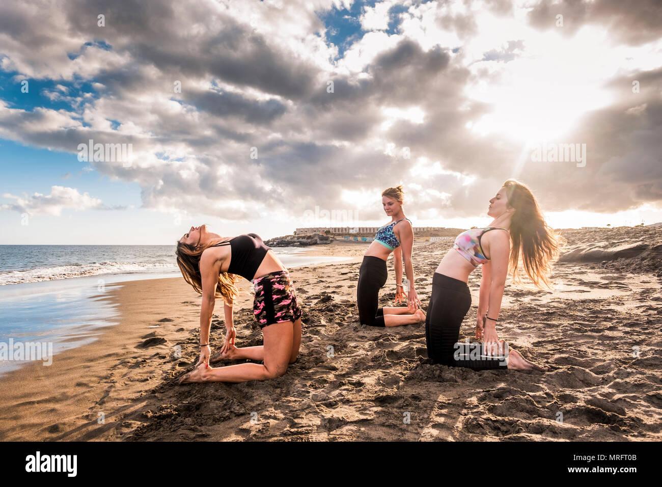 Pilates und Lektion für eine Gruppe von Menschen am Strand. Drei junge schöne Modell Frauen Fitness am Ufer in der Nähe des Ozeans Wasser. Wunder Stockbild