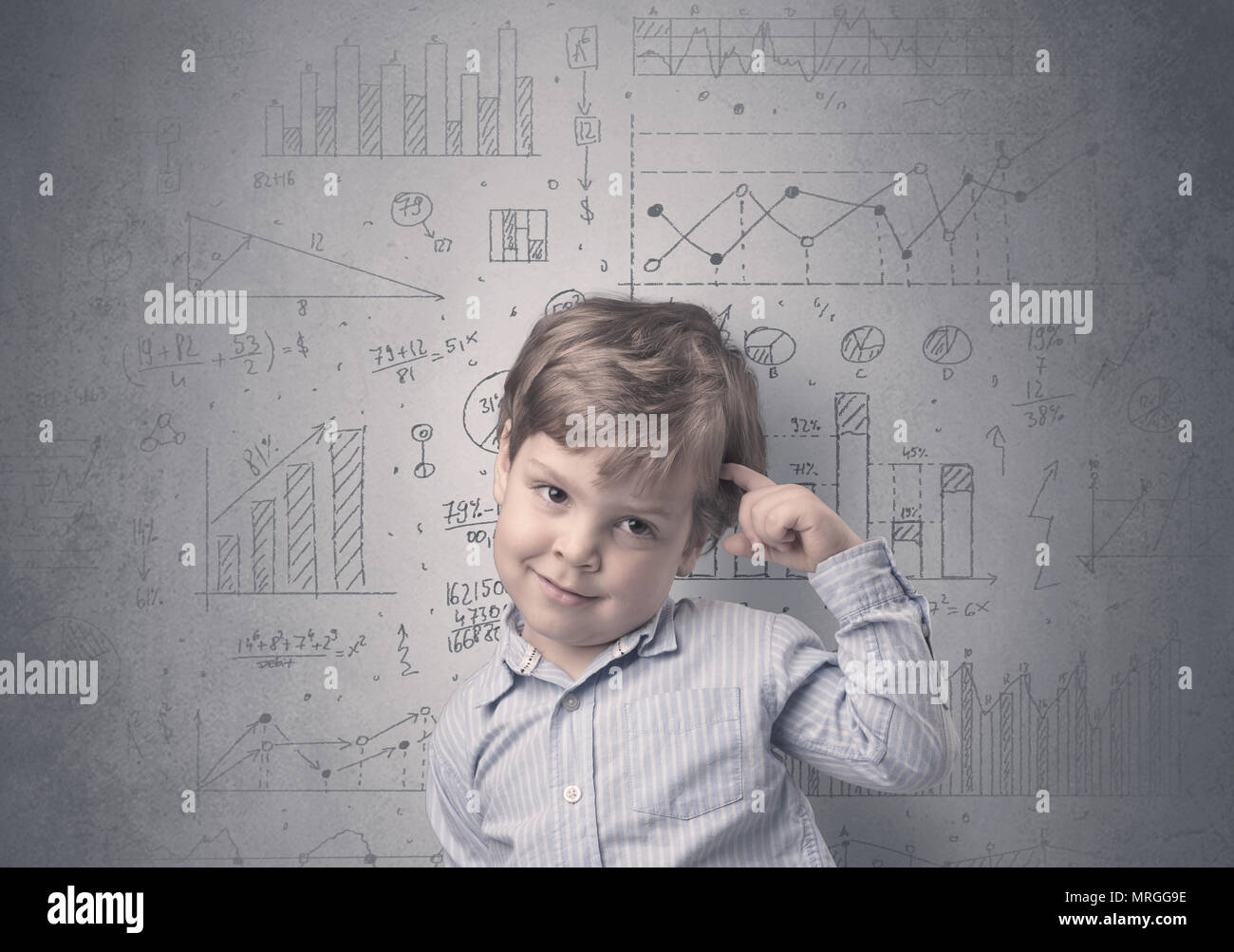 Kleiner Junge vor einer grauen Wand mit Graphiken und Statistiken um Stockbild