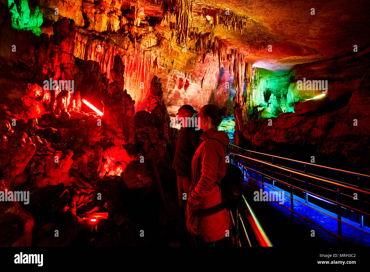 Touristische Paar in unterirdische Höhle Sataplia mit bunten Beleuchtung in Kutaissi, Georgien Stockbild