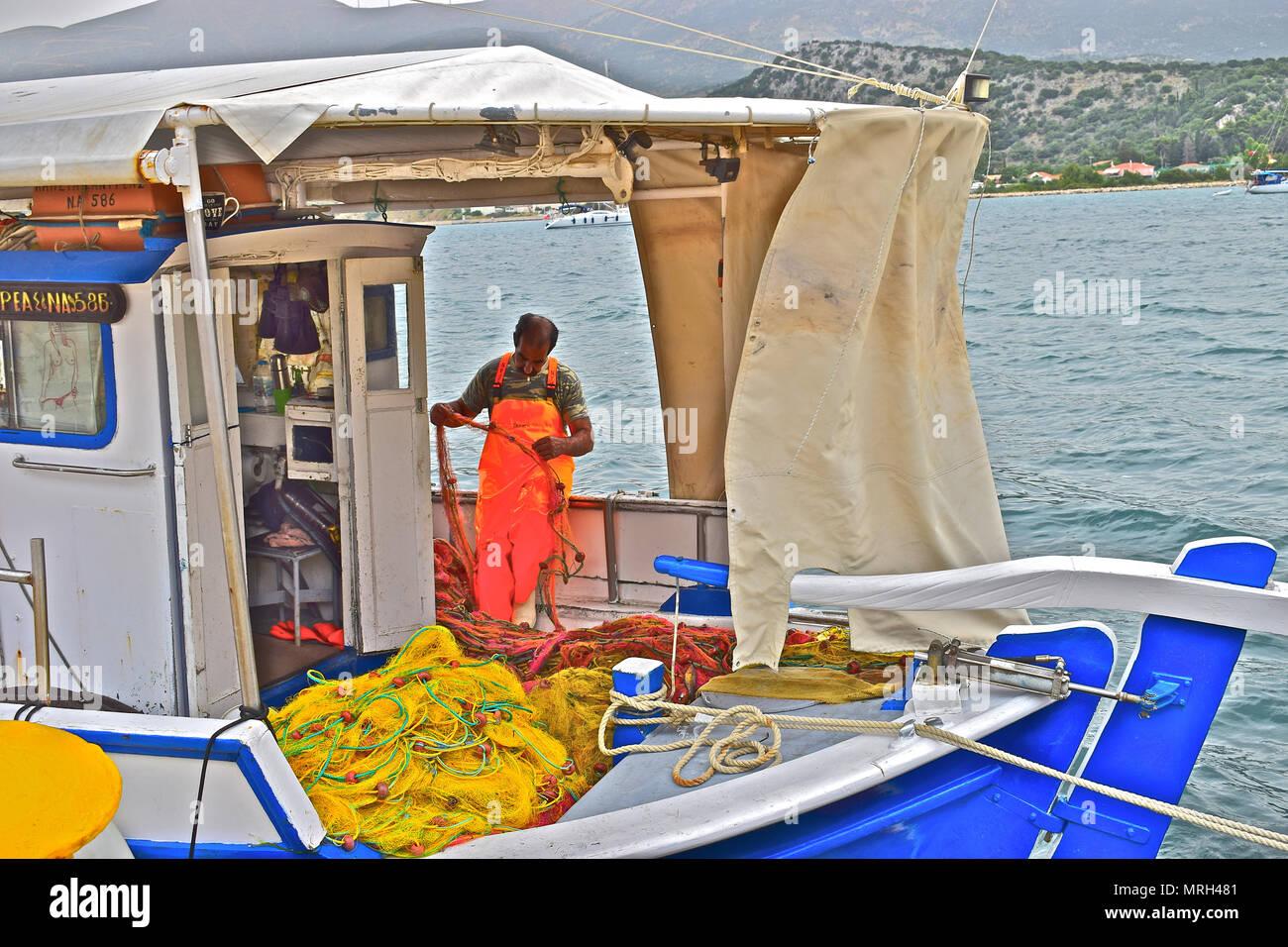 Griechische fischer Flicken der Netze an Bord seines kleinen Boot im Hafen der Hauptstadt Argostolis in Kefalonia Kefalonia/Griechenland Stockfoto