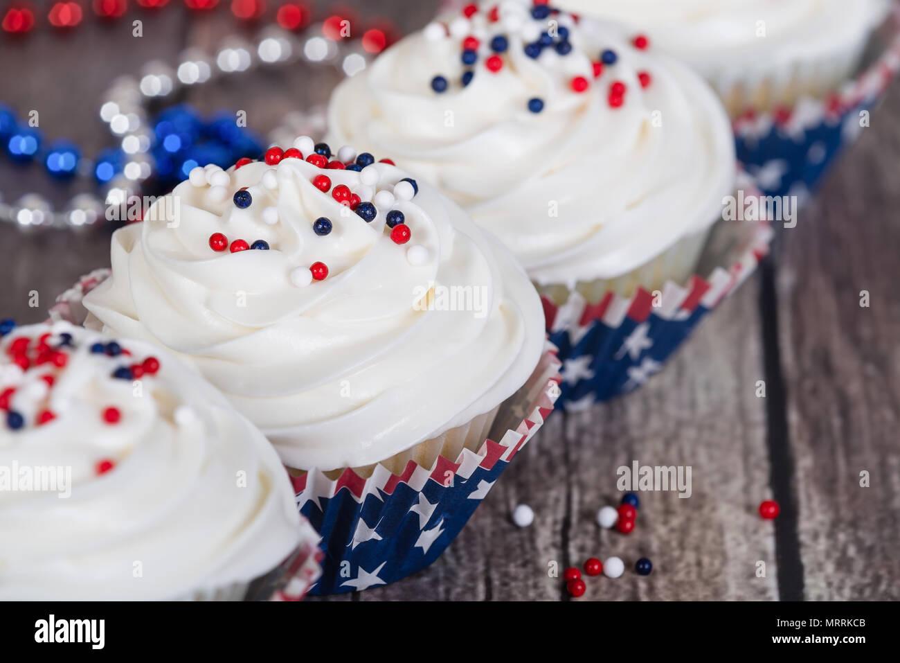 Patriotische 4. Juli oder Memorial Day Feier Cupcakes auf rustikalen Holztisch mit festlichen roten, weißen und blauen Verzierungen. Stockfoto