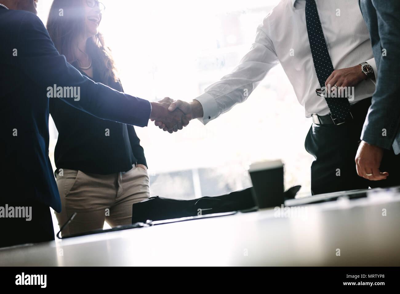 Partner Abschluss und Händeschütteln in Anwesenheit von Mitgliedern des Teams. Unternehmer die Hände schütteln im Board Room und Beenden einer Sitzung. Stockbild