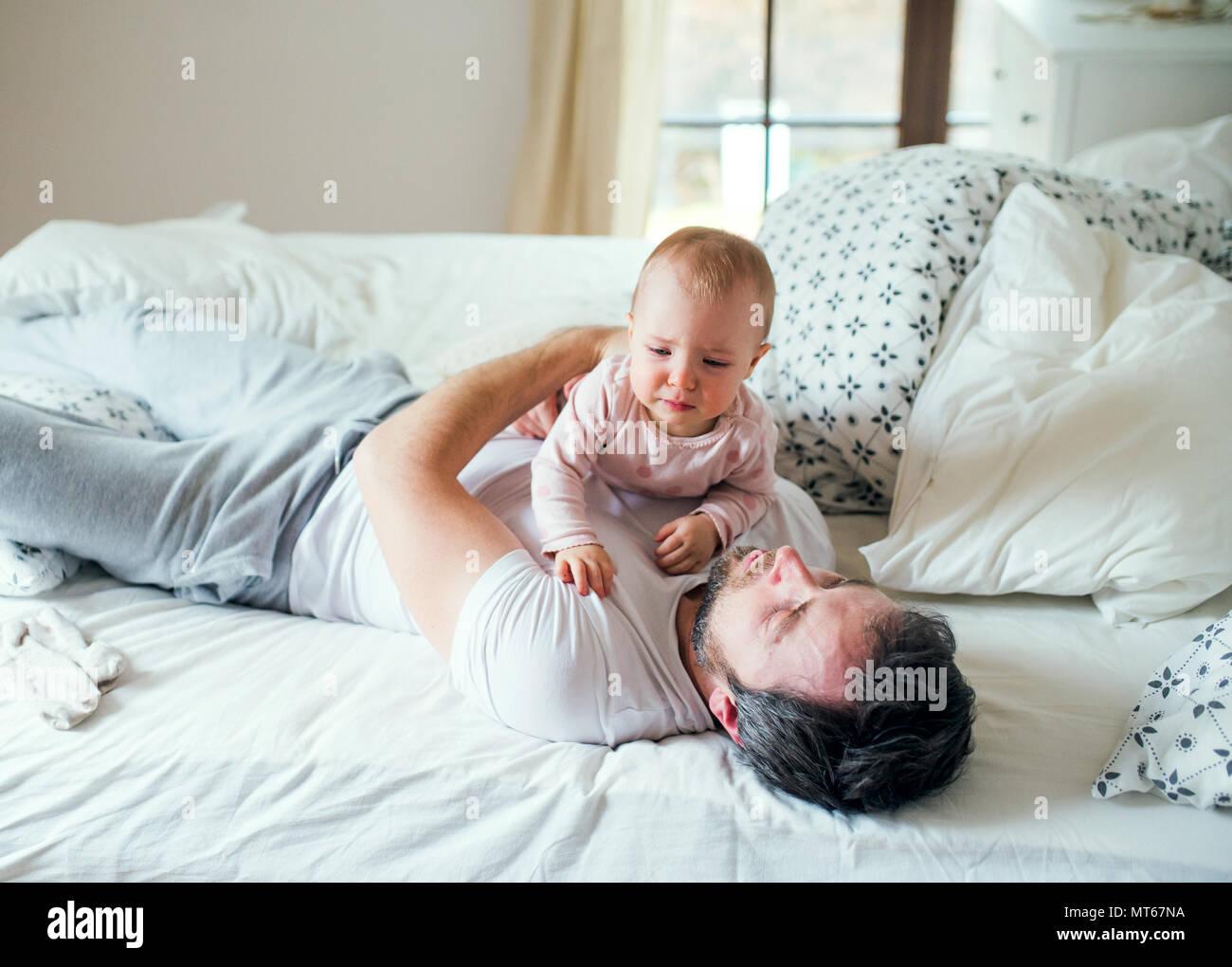Vater mit einem Kleinkind Mädchen auf dem Bett zu Hause vor dem Schlafengehen. Stockfoto