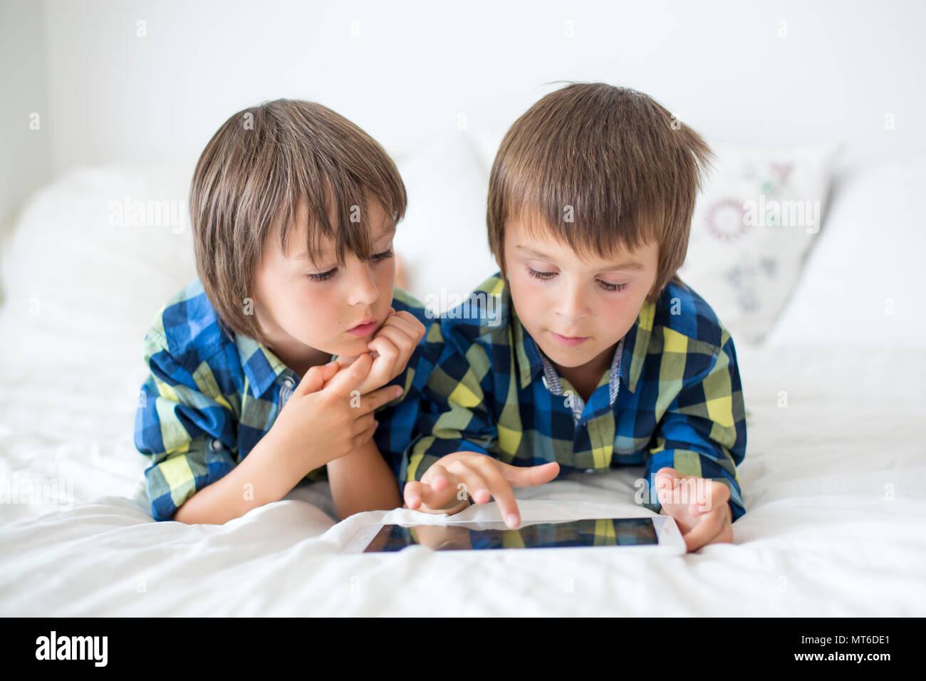 Zwei Kinder im Vorschulalter, junge Brüder, zu Hause im Bett auf Tablet Stockbild