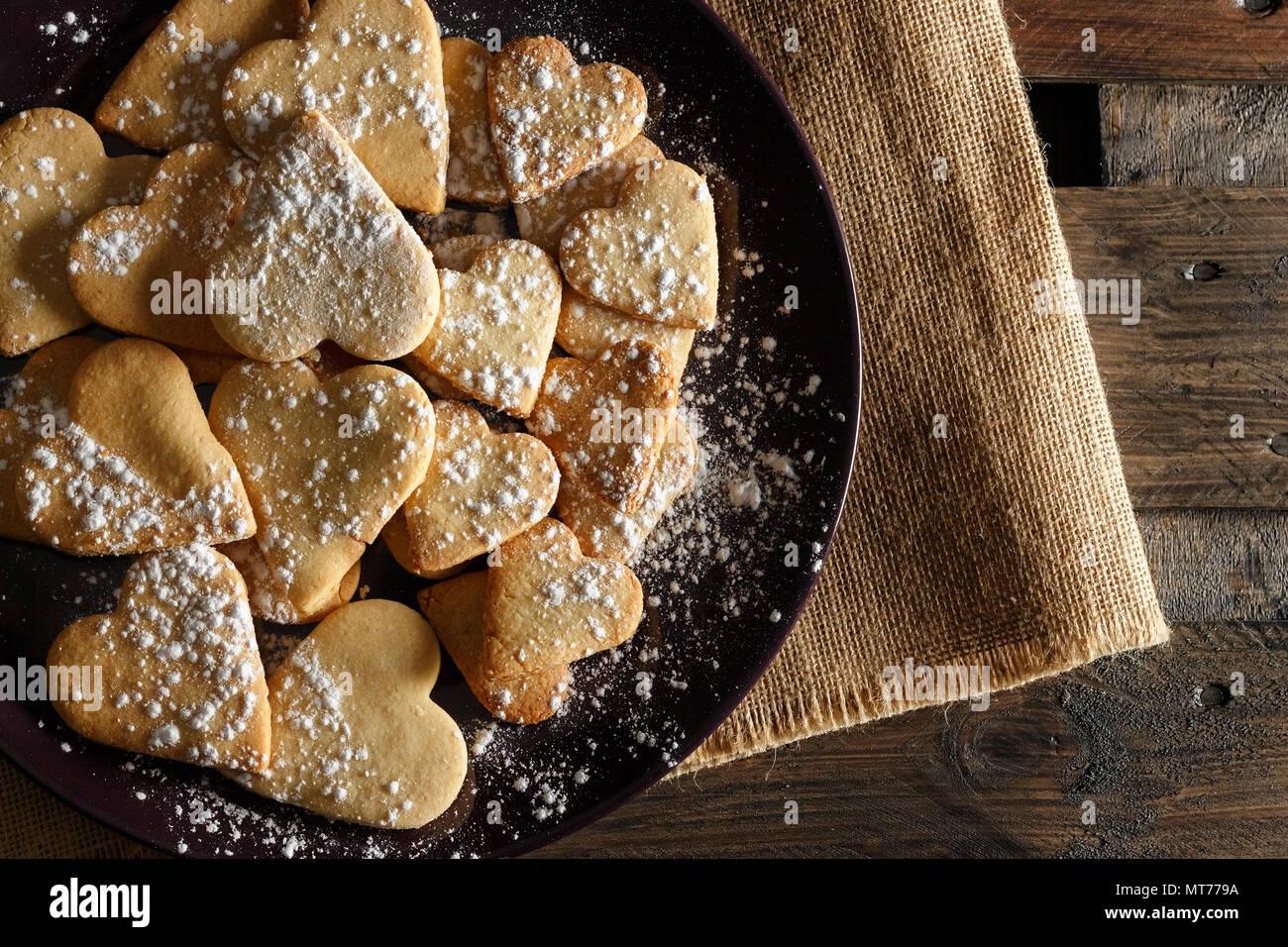 Köstliche hausgemachte herzförmige Plätzchen mit Puderzucker auf Sack und Holzbretter bestreut. Bild horizontal von oben gesehen. Stockbild