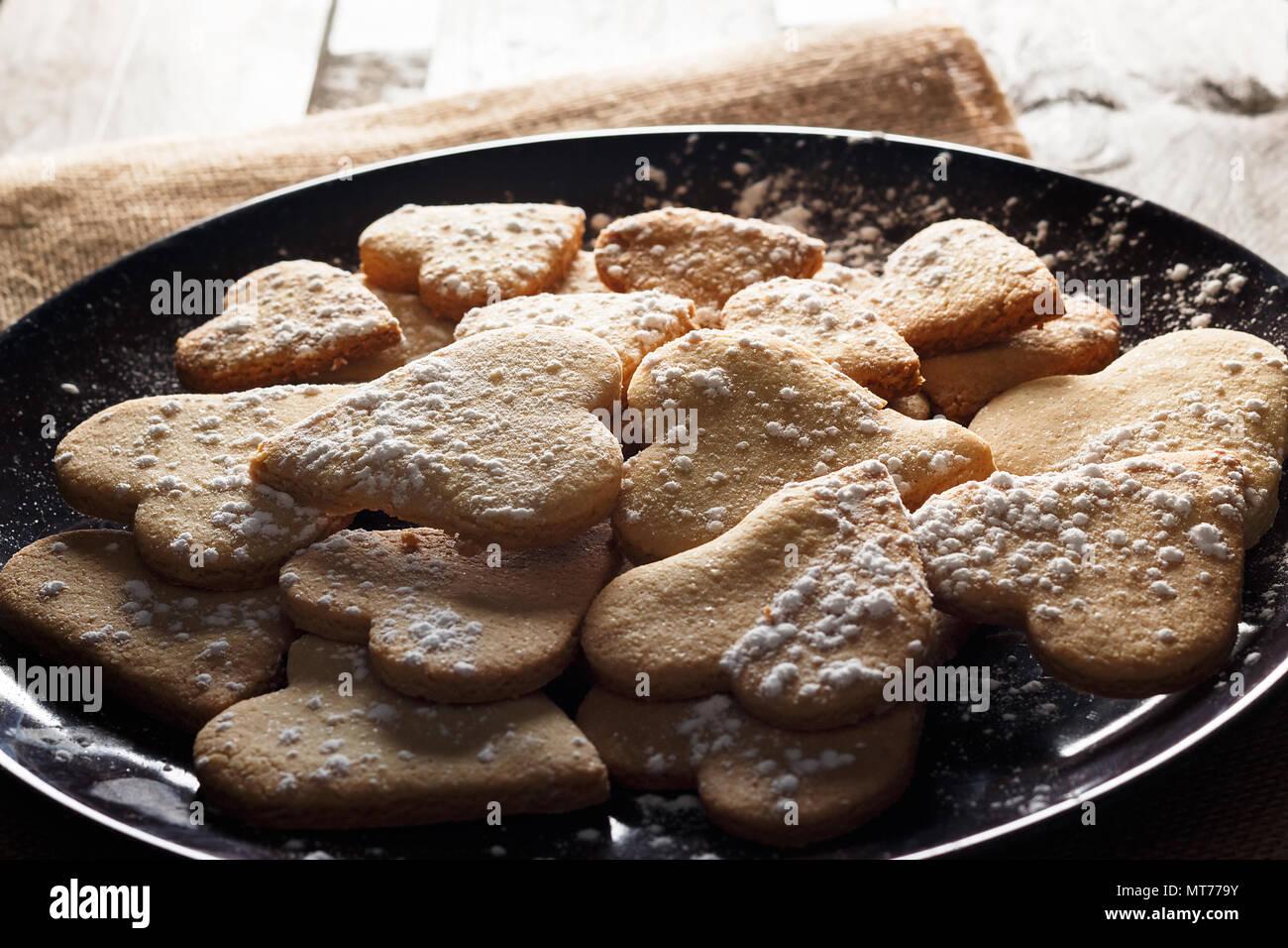 Köstliche hausgemachte herzförmige Plätzchen mit Puderzucker auf Sack und Holzbretter bestreut. Bild horizontal gegen Hintergrundbeleuchtung gesehen. Stockbild