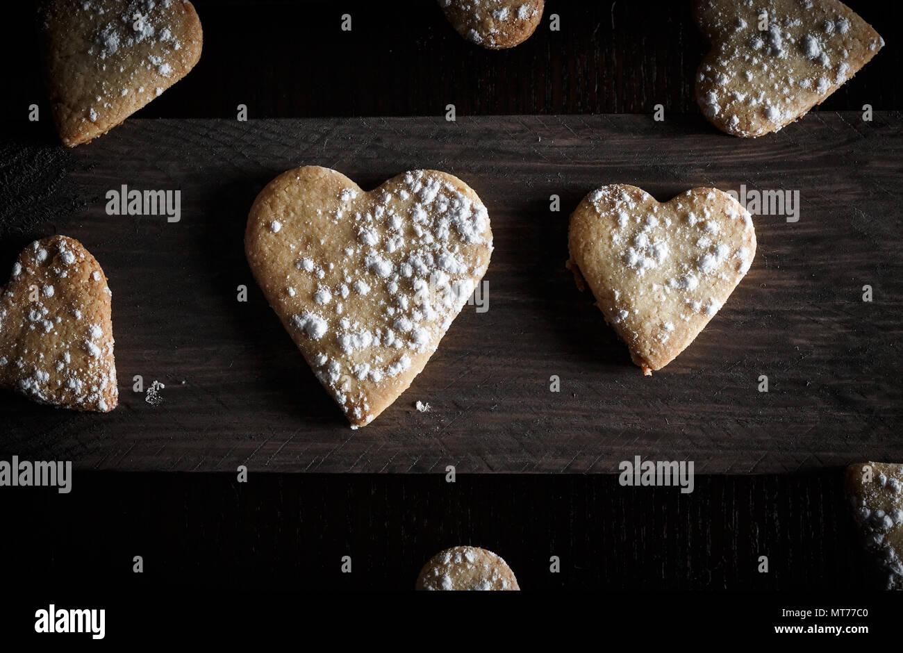 Köstliche hausgemachte herzförmige Plätzchen mit Puderzucker in eine Holzplatte bestreut. Bild horizontal von oben gesehen. Dunkle moody Stil. Stockbild