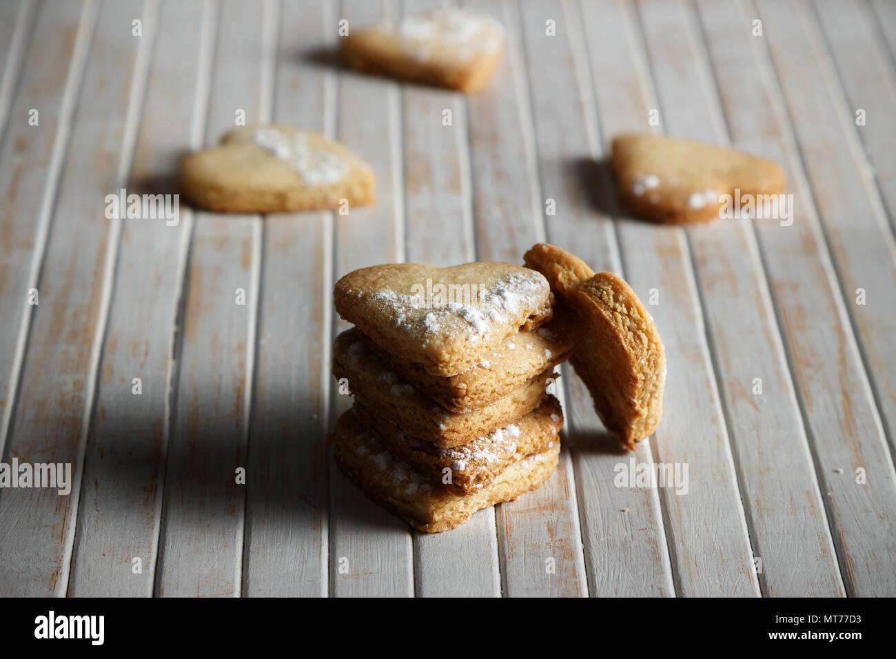 Köstliche hausgemachte herzförmige Plätzchen mit Puderzucker in eine Holzplatte bestreut. Bild horizontal. Dunkle moody Stil. Stockbild
