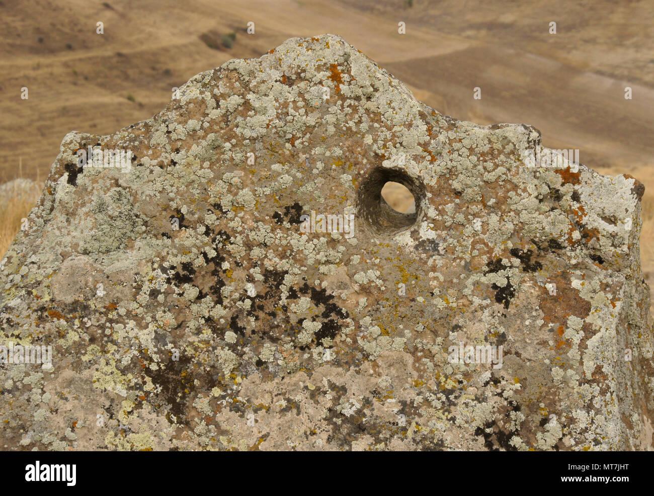 Flechten - verkrustete Rock mit Loch gebohrt, Karahunj (Carahunge) Sternwarte in der Nähe der Stadt Sisian, Armenien Stockfoto