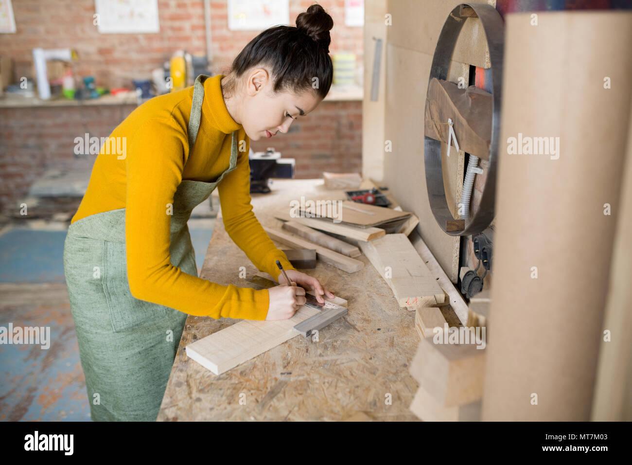 Weibliche Handwerker arbeiten mit Holz Stockfoto