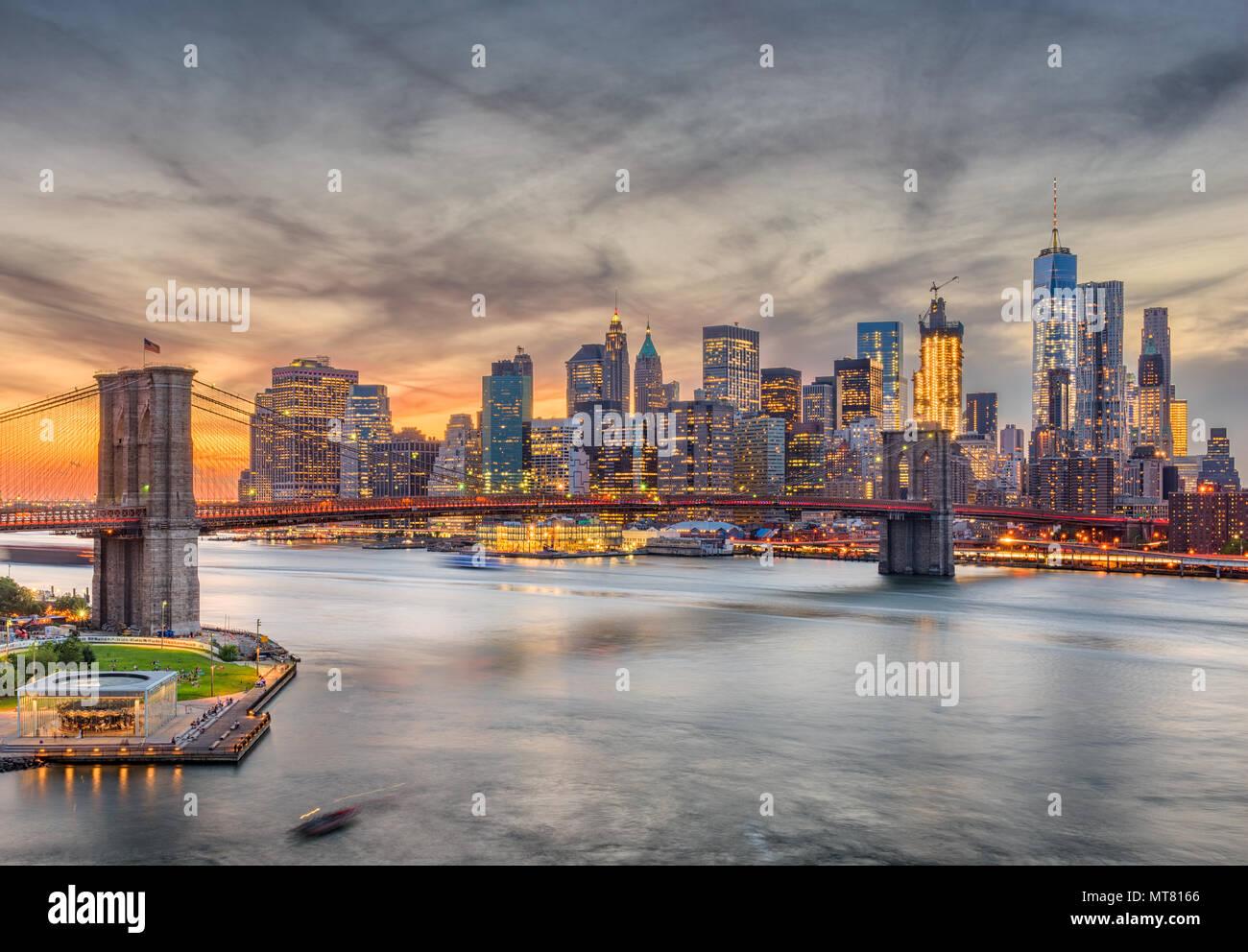 New York, New York, USA Skyline von Manhattan über den East River und die Brooklyn Bridge nach Sonnenuntergang. Stockbild
