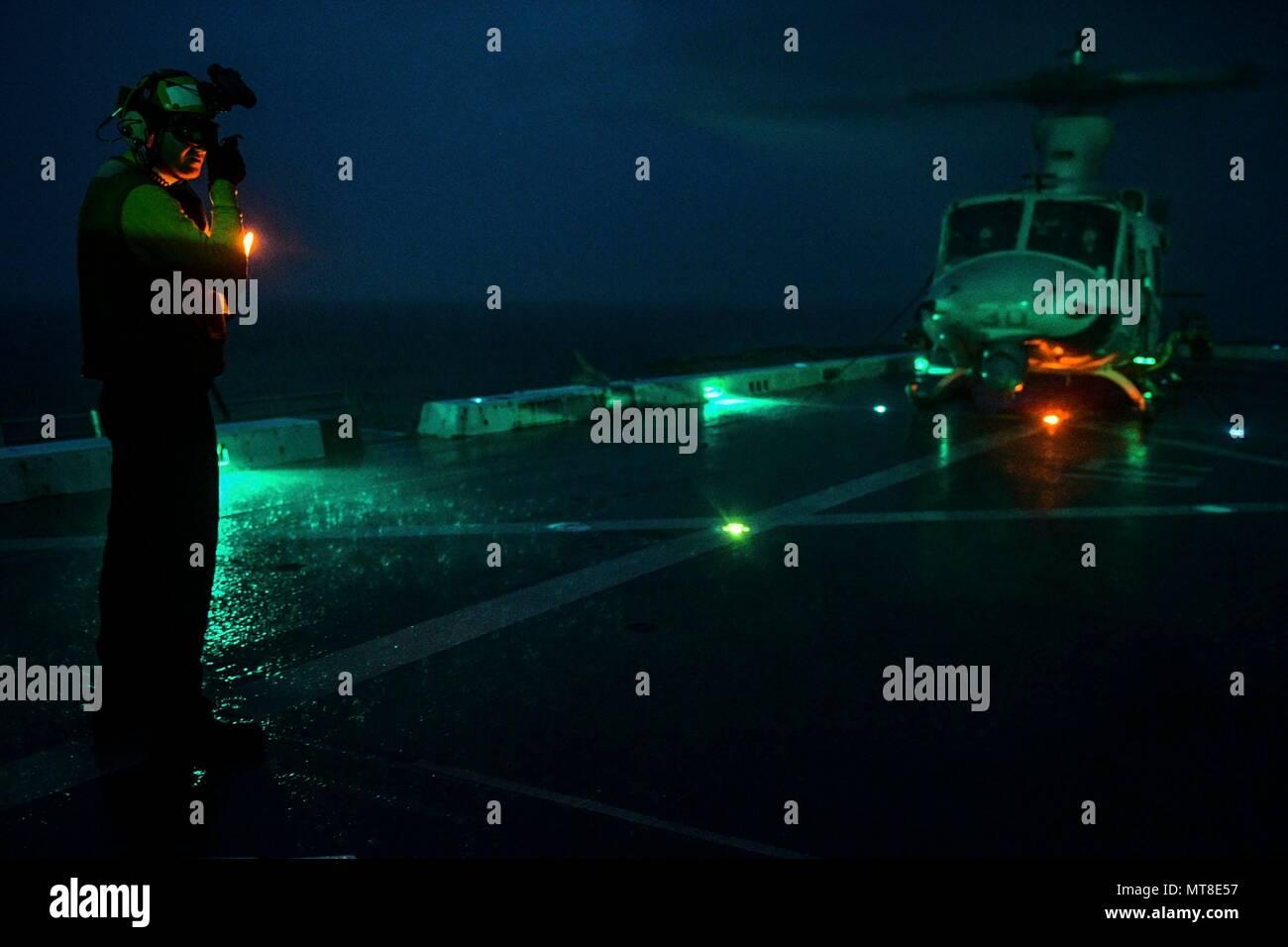 Indischer Ozean (31. 30, 2017) Aviation Bootsmann Mate Handhabung Airman Ryan Sharland, aus Newport Beach, Calif., leitet ein UH-1Y Venom, zugeordnet zu den Marine Medium Tiltrotor Squadron (VMM) 161 (verstärkt), auf dem Flugdeck des amphibious Transport dock Schiff USS San Diego LPD (22). San Diego, Teil der Amerika amphibischen bereit, Gruppe, mit Eingeschifft 15 MEU, arbeitet in der Indo-Asia - Pacificregion Partnerschaften zu stärken und dienen als ready-Response Force für jede Art von Kontingenz. (U.S. Marine Foto von Mass Communication Specialist 3. Klasse Justin A. Schoenberger/Freigegeben) Stockfoto