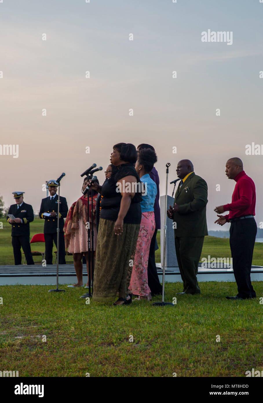Eine Familie singt Lieder zusammen während der jährlichen Easter Sunrise Zeremonie, Camp Lejeune, N.C., 16. April 2017. Jedes Jahr das Marine Corps Installationen Osten Kaplan hosts Die Easter Sunrise Zeremonie für die Marines und Seeleute, ihre Familien zu bringen und das Osterfest feiern. Stockbild