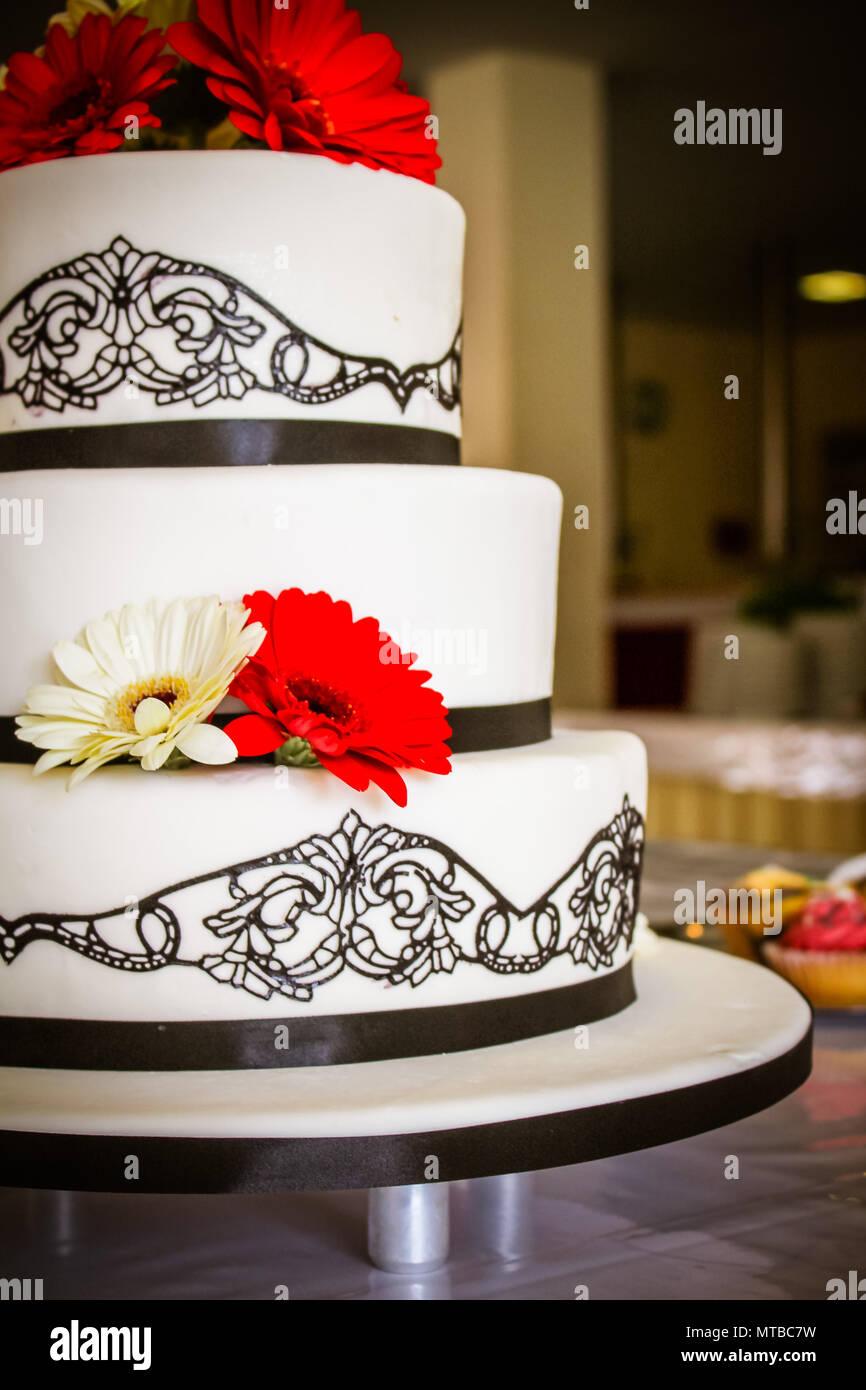 Die Hochzeitstorte mit roten Gerbera Stockbild