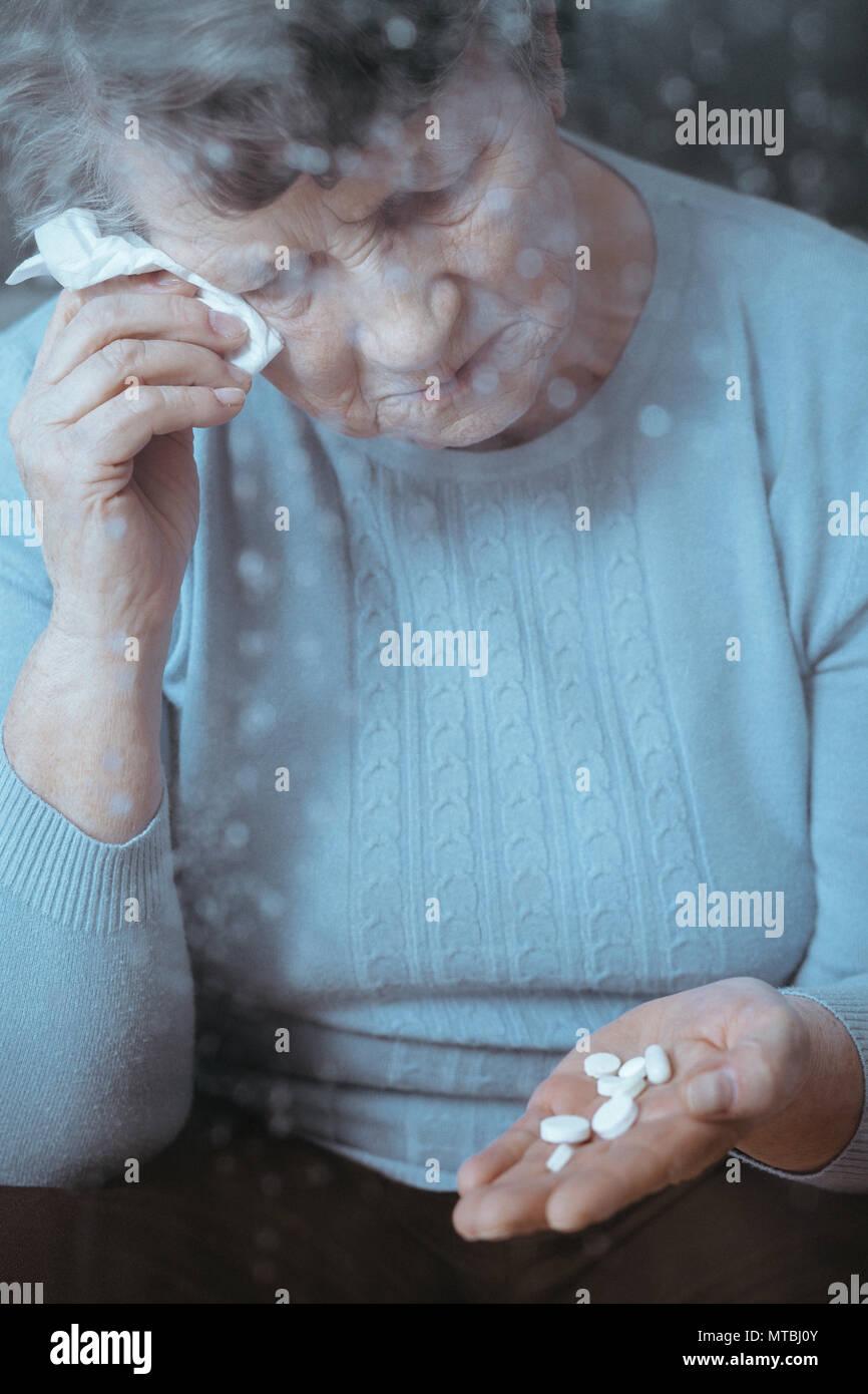 Kranke ältere Frau weinen, holding Pillen in der Hand Stockfoto