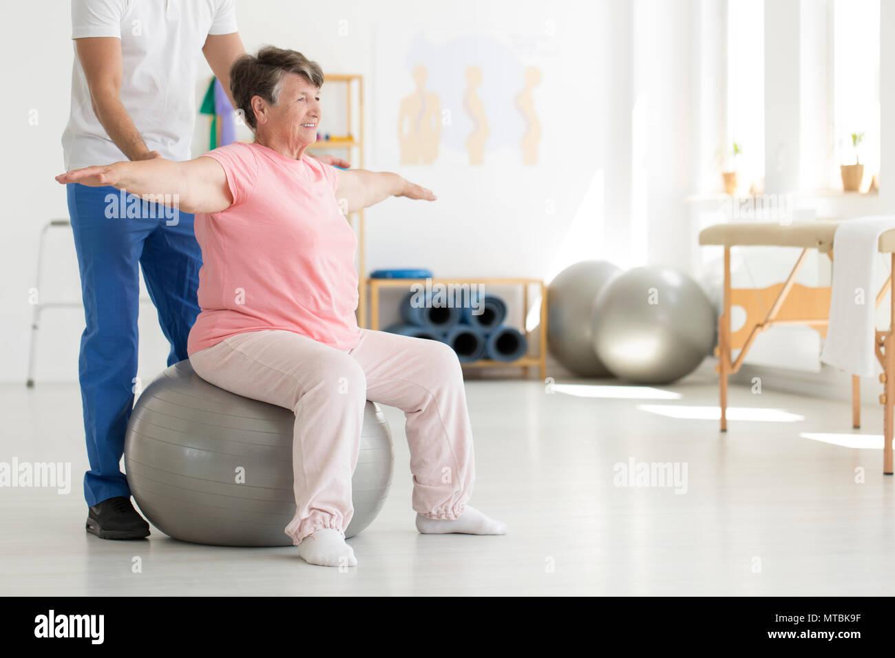 Ältere ältere Gemeinde versuchen, das Gleichgewicht zu halten, während er auf dem grauen Fit Ball, während durch die physiotherapeutin unterstützt werden Stockbild