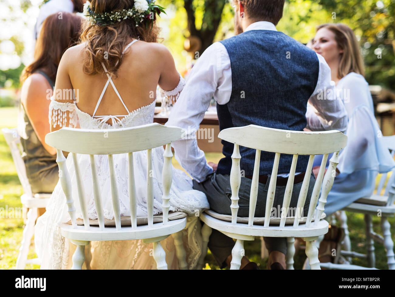 Braut und Bräutigam mit Gästen in Hochzeit außerhalb im Hinterhof. Stockbild