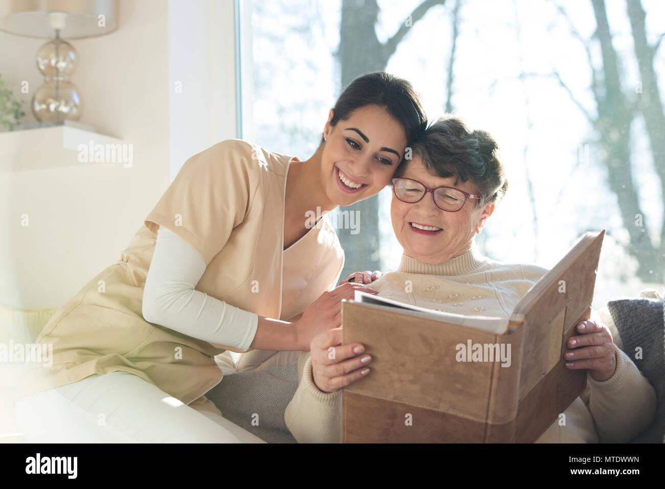 Geriatrische Patienten mit Demenz zusammen mit einer beruflichen Rehabilitation Krankenschwester an einem Familie Foto Album in einem privaten betreutes Wohnen Haus suchen Stockbild
