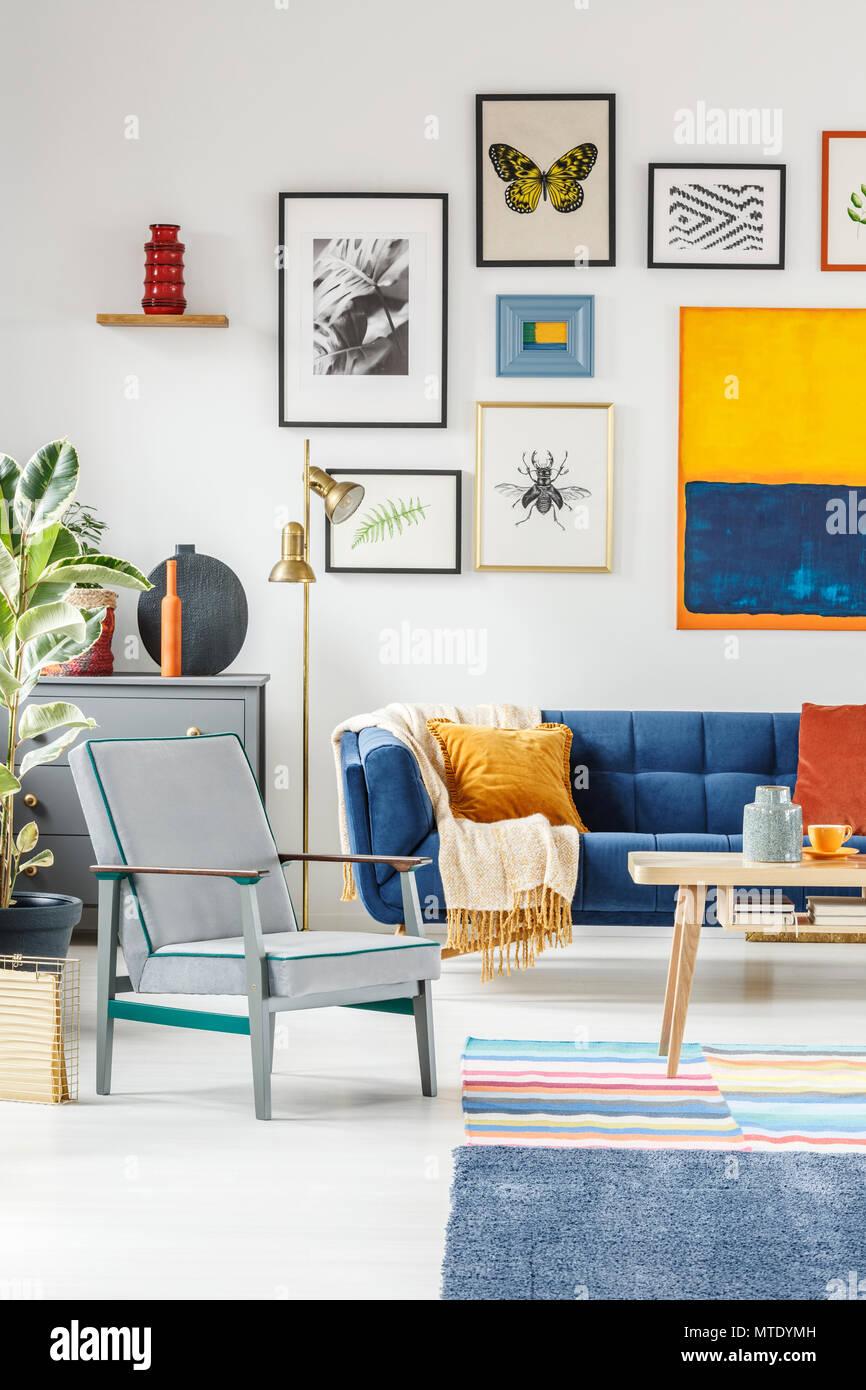 Real Photo Eines Boho Wohnzimmer Innenraum Mit Einer Galerie Von Plakaten  An Den Weißen Wand über Einen Grauen Sessel Und Blaue Couch