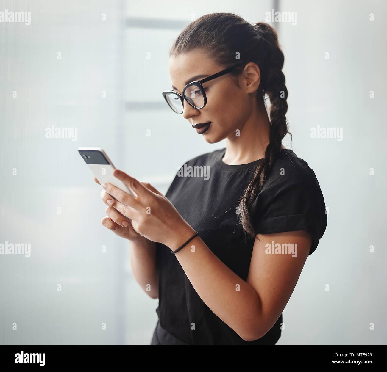 Junge brünette Mädchen mit Brille und schwarzen Lippenstift holding Handy Stockbild