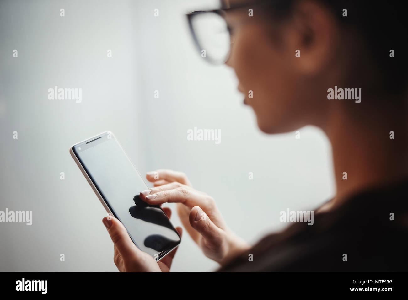 Junge brünette Mädchen mit Brille holding Handy- und Entriegelung. Mädchen ist auf Vorder- und verschwommen, mobile ist auf Hintergrund und Fokus. Stockbild