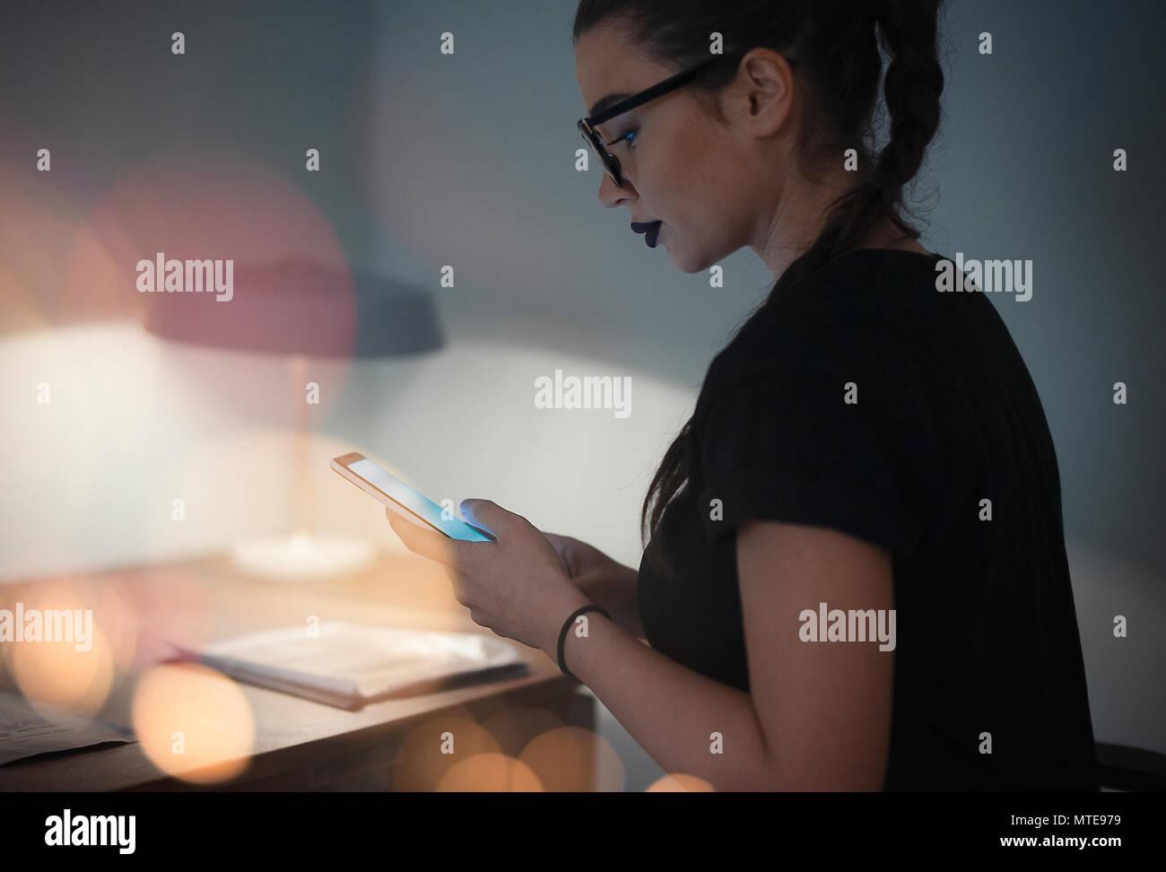 Junge brünette Mädchen mit Brille, Handy Stockbild