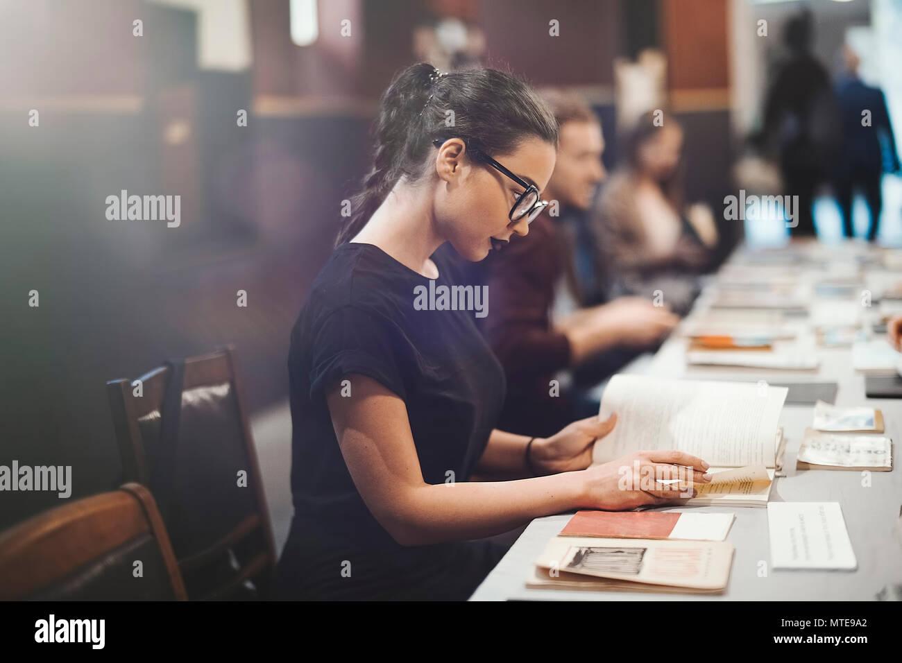 Junge brünette Mädchen mit Brille und schwarzen Lippenstift lesen Buch Stockbild