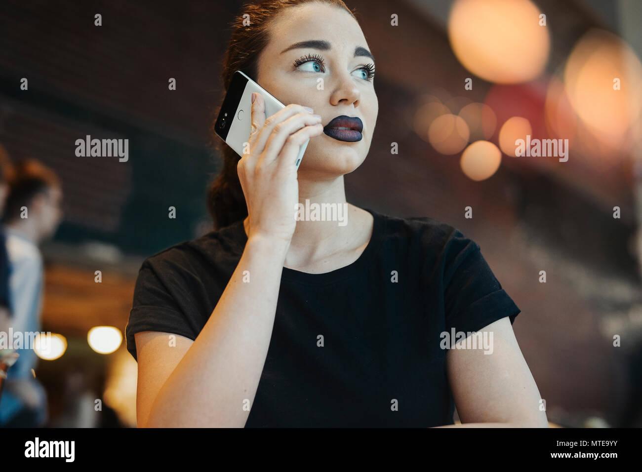 Junge brünette Mädchen mit Brille im Gespräch per Handy Stockbild