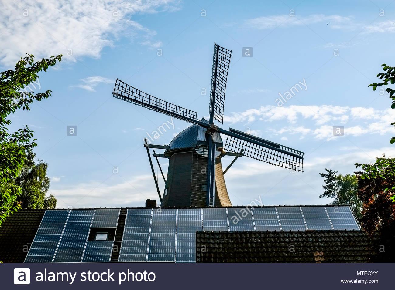 Traditionelle Windmühle mit Photovoltaik Solar Panels in Ramsloh, Saterland, Niedersachsen, Norddeutschland. Stockbild