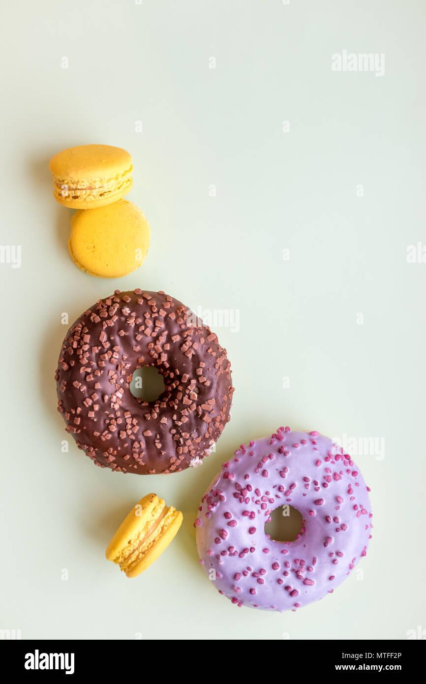 Glasierte Krapfen und Makronen. Süße Nachspeise auf weichen, grünen Hintergrund isoliert. Kuchen mit buttercream. Zitronensaft, gelb Macaron Cookies. Pop Art farbe Stil. Selektive konzentrieren. Platz kopieren Stockbild