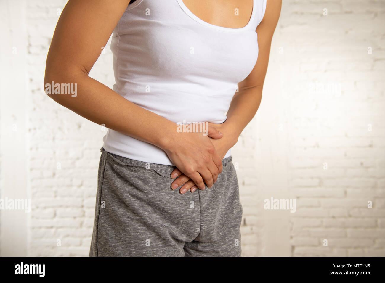 Nahaufnahme von einer jungen Frau, schmerzliche Magenschmerzen, Hände auf ihren Bauch. Körper Schmerzen, Gastritis, Verstopfung, Schmerzen und Krämpfe. Stockbild