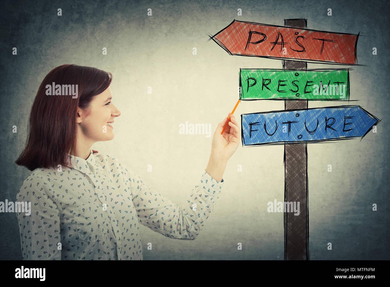 Lächelnden jungen Geschäftsfrau Zeichnung ein Wegweiser mit Pfeilen, die Vergangenheit, die Gegenwart und die Zukunft zeigt. In der Zeit bunte Schild verloren, destiny Evolution con Stockbild