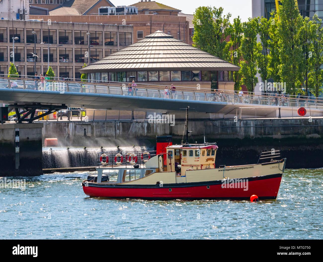 Mona Titanic Tour Boot vor dem Wehr verankert. Der Lagan Lookout ist im Hintergrund Stockfoto