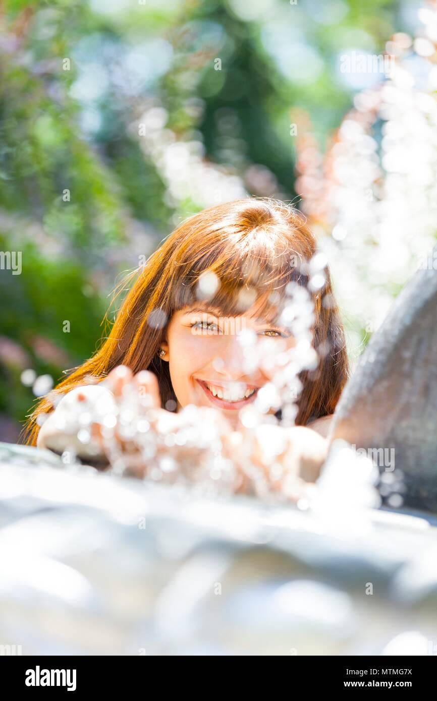 Hübsche weibliche junge Frau Teenager headshot hinter Sprühwasser lachen sehr glücklich lächelnd und fröhlich Stockbild