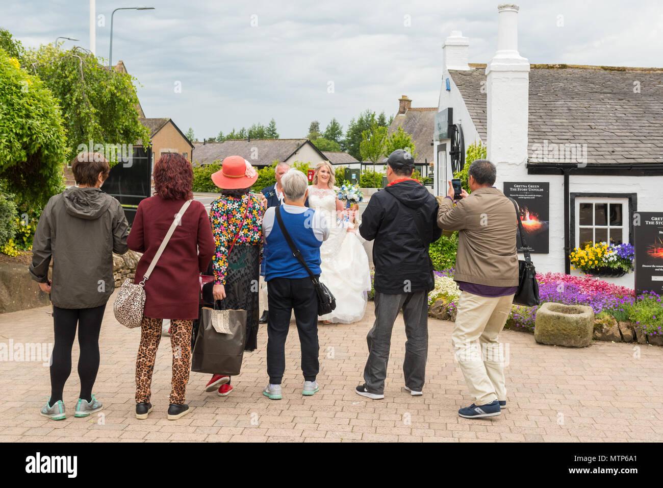 Asiatische Touristen fotografieren einer Braut ankommen für Ihre Hochzeit in Gretna Green, Schottland, Großbritannien Stockbild