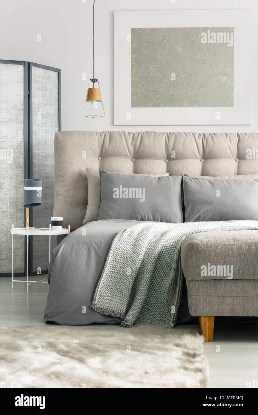 Grau Gemutliches Schlafzimmer Mit Einem Bequemen Bett Und Osmanischen Stockfotografie Alamy
