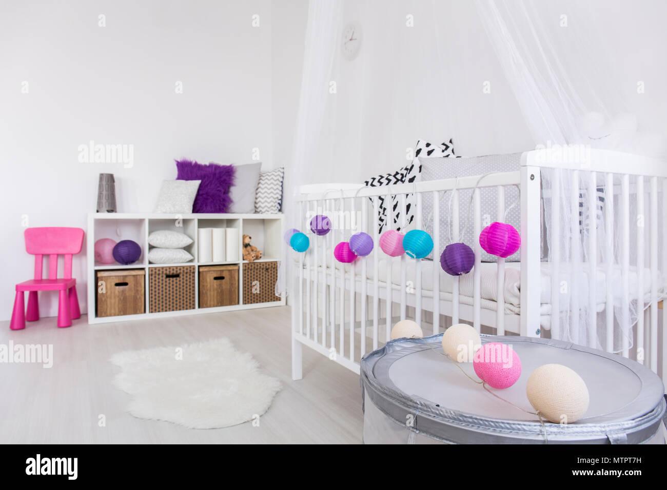 Modern gestaltetes Interieur Baby's Schlafzimmer mit weißen Wiege mit bunten Kugeln geschmückt. An der gegenüberliegenden Wand Regal mit Boxen und Kissen Stockfoto