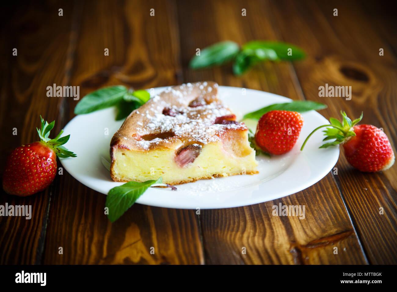 Hüttenkäse süßer Auflauf mit Erdbeeren auf einem Holztisch Stockbild