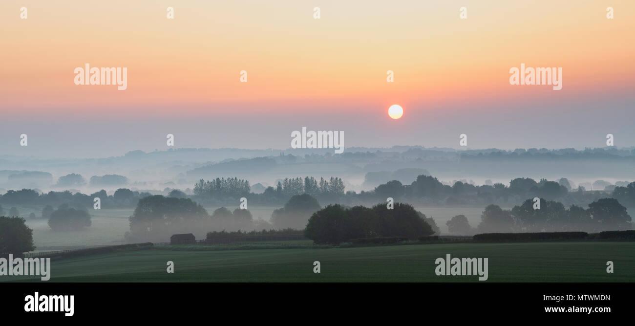 Nebliger Sonnenaufgang im Frühjahr über die Landschaft von Warwickshire in der Nähe von Stratford-upon-Avon. Warwickshire, Großbritannien. Panoramablick Stockbild