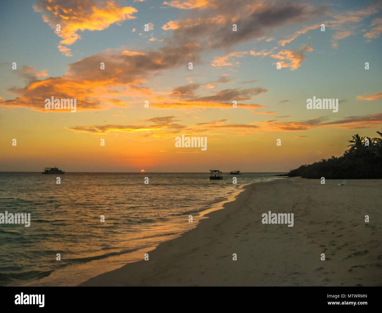 Malediven Hintergrund. Sonnenuntergang über dem tropischen Meer und Coral Beach mit bunten Wolken im Himmel. Boote am Horizont in der himmlischen Atoll der Ruhe und Entspannung. Nord Male Atoll Asdu, Indischer Ozean. Stockfoto