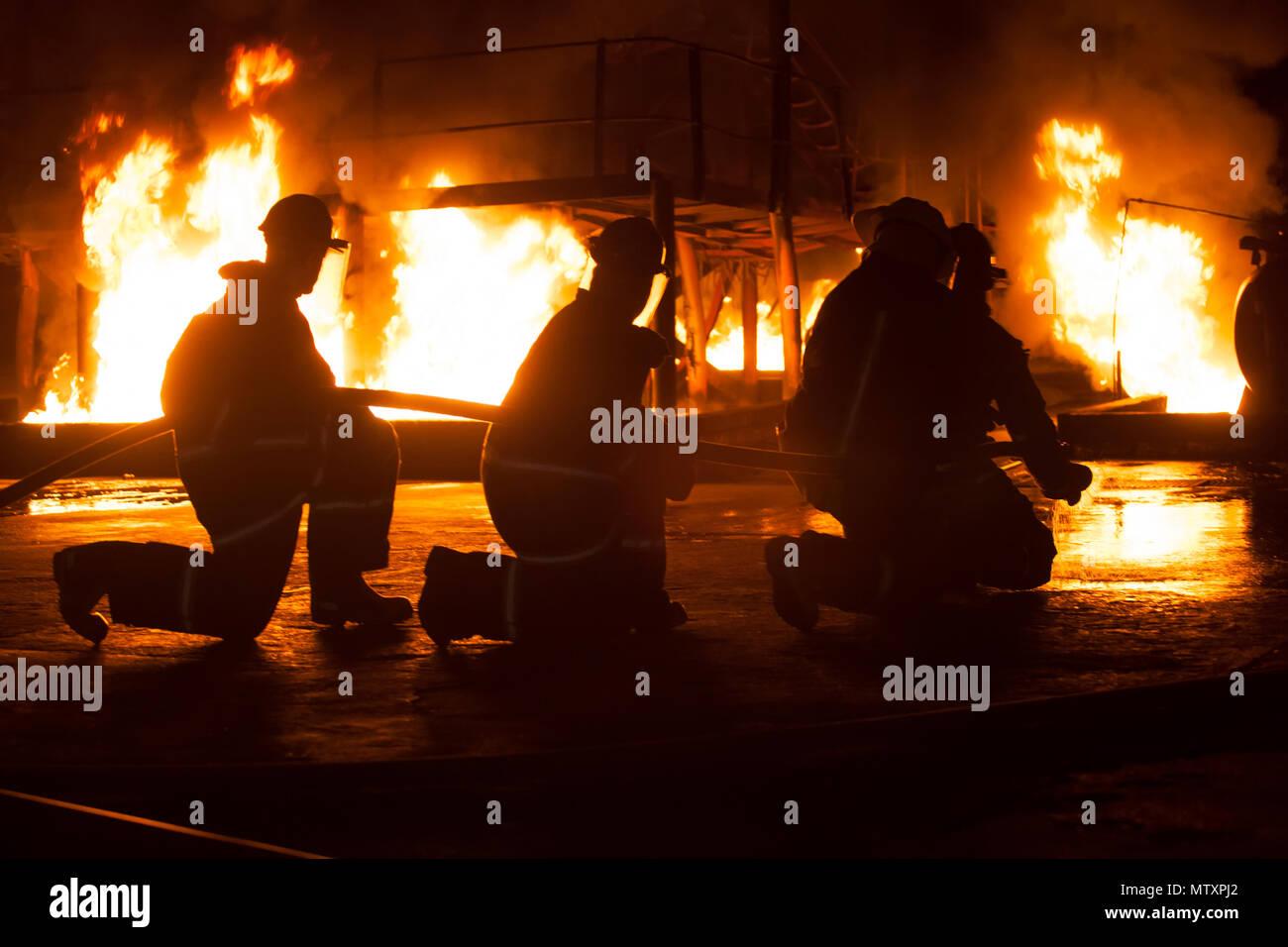 JOHANNESBURG, Südafrika - Mai, 2018 Feuerwehrmänner knien während der Brandbekämpfung Training Stockfoto