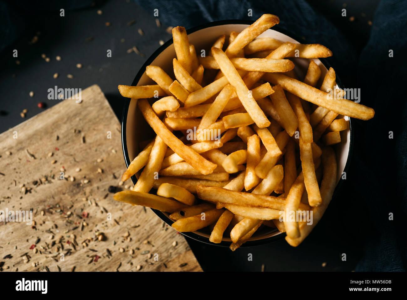 High Angle Shot einige leckere Pommes frites in eine weiße keramische Schüssel serviert, auf einem dunkelgrauen rustikalen Holztisch gelegt Stockbild