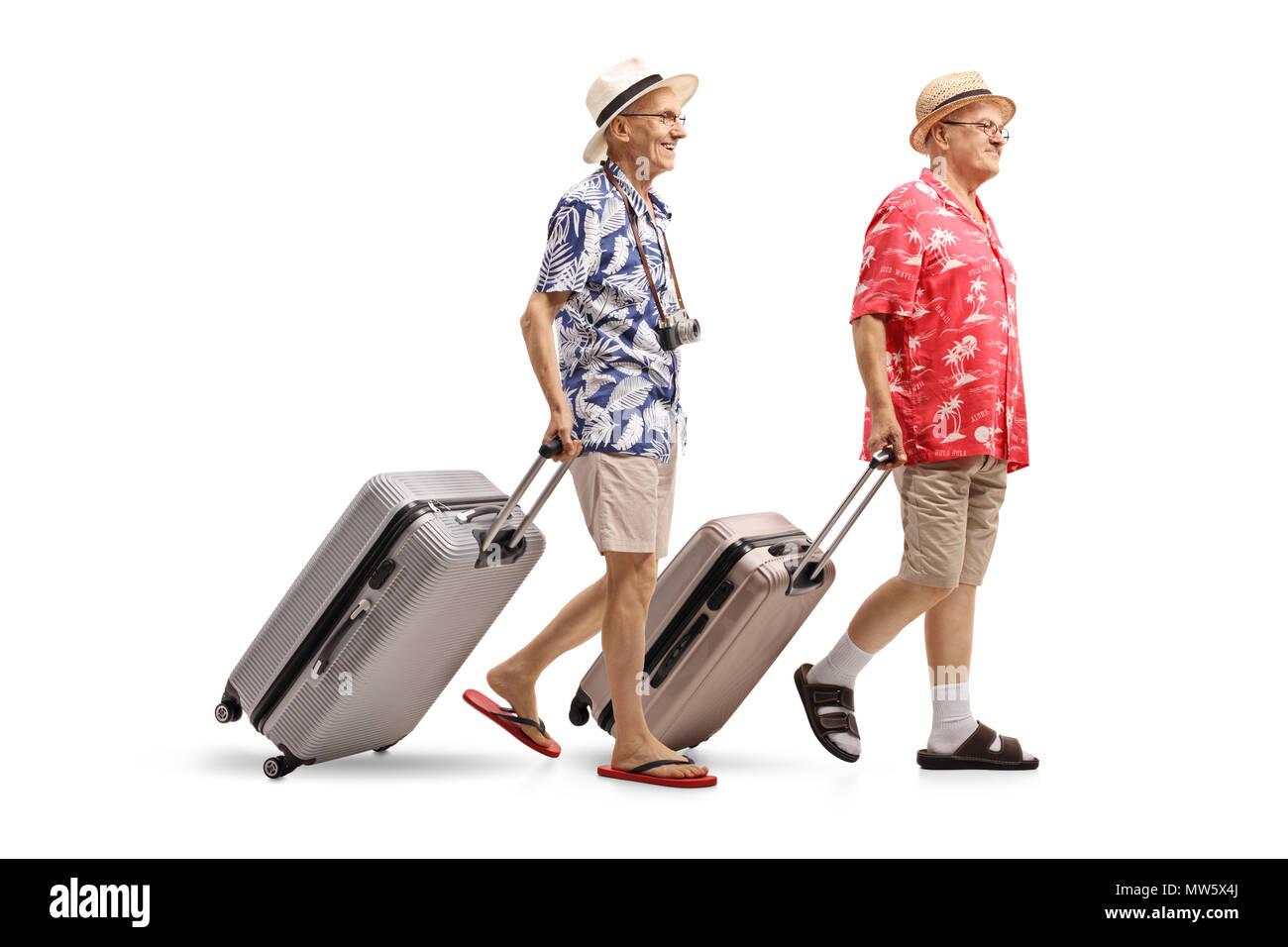 Volle Länge Profil Schuß von zwei älteren Touristen mit Koffern zu Fuß auf weißem Hintergrund Stockbild