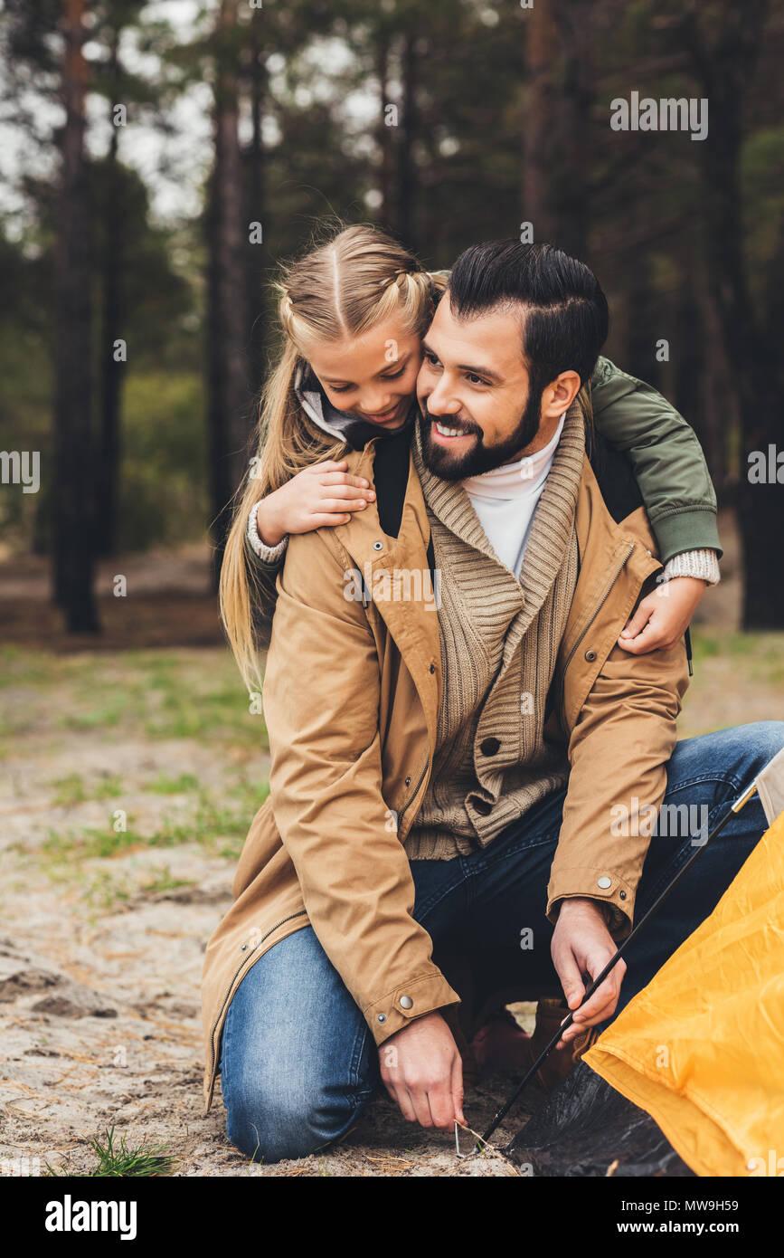 Glücklich aussehenden Vater intalling camping Zelt, während Tochter umfing ihn Stockbild