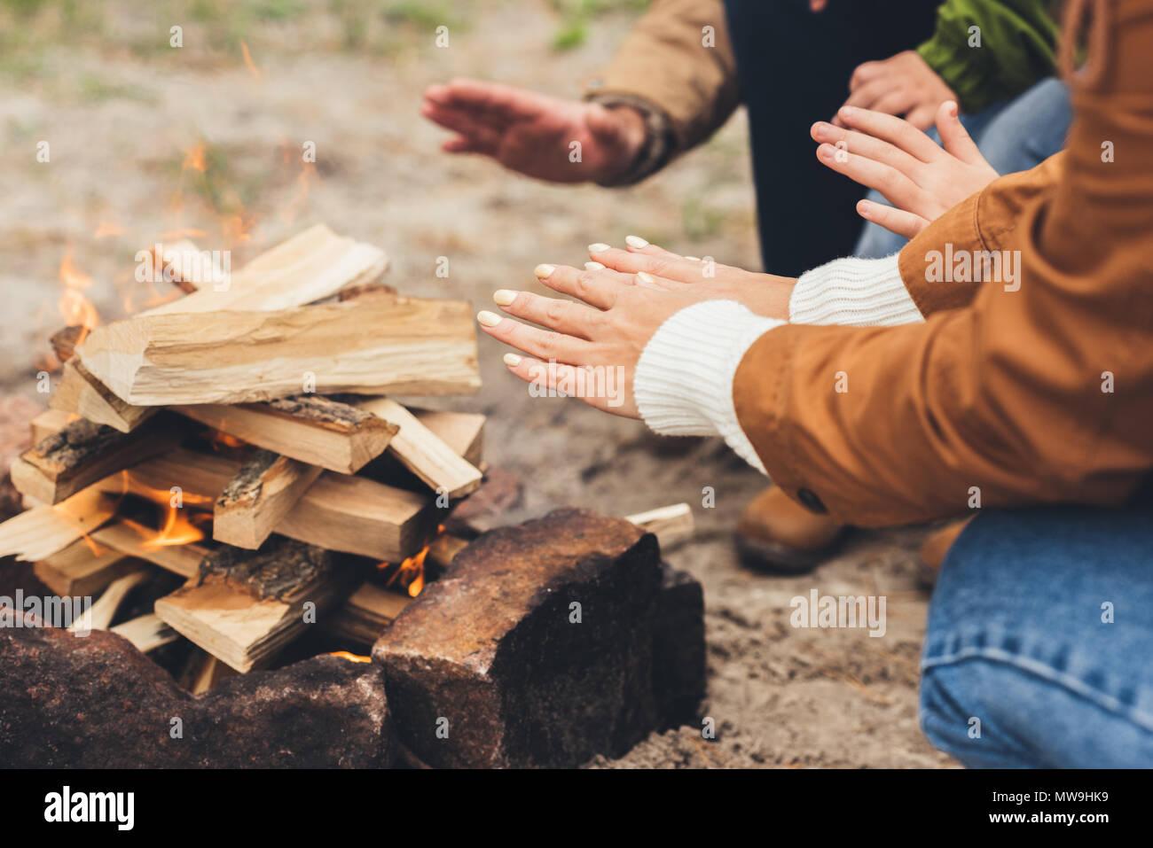 7/8 Schuß von Menschen Erwärmung der Hände mit Lagerfeuer Stockbild