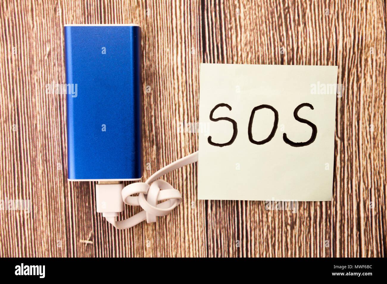 SOS handschriftliche Wort auf weißem Papier oben retro Holz- Rinde Hintergrund. Konzept mit Hilfe Zeichen auf dem weißen Papier. Speichern unsere Seelen handschriftlichen Zeichen auf dem weißen Papier. Stockfoto